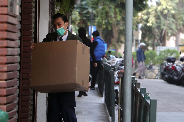 man in black jacket carrying brown cardboard box to protect from coronavirus